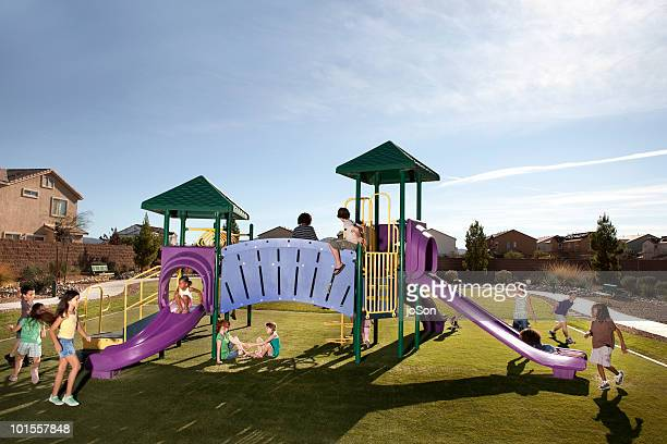 kids playing on playground slides outdoors - spielgerät stock-fotos und bilder