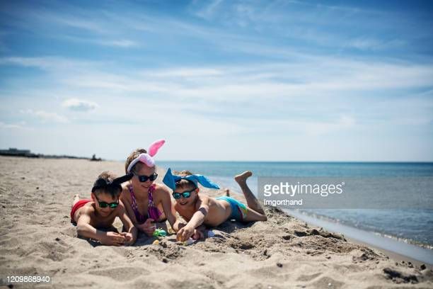 kids playing on the beach with easter eggs - italian easter stock pictures, royalty-free photos & images