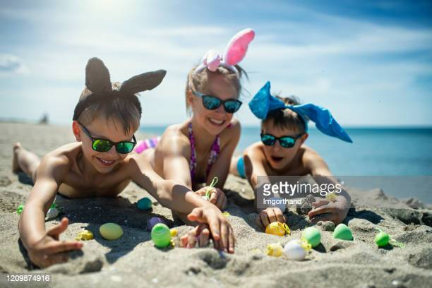 kids playing on the beach with easter eggs - easter beach stock pictures, royalty-free photos & images