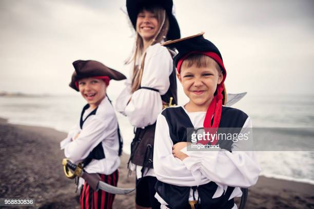 kids playing pirates on a beach - halloween beach stock photos and pictures