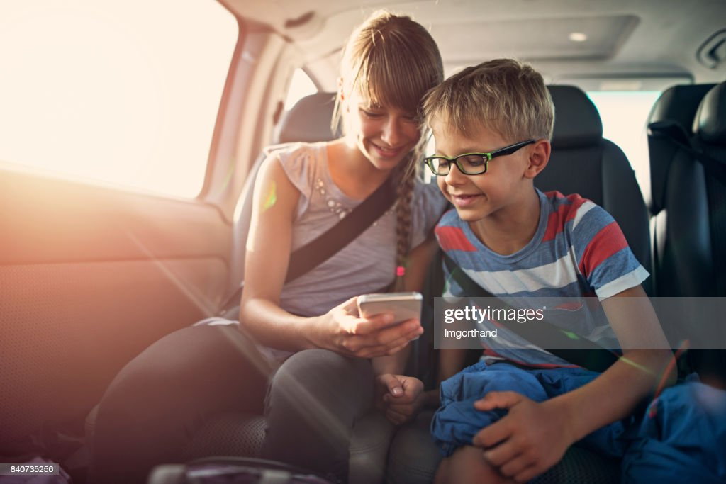 Kids playing smartphone during a road trip : Stock Photo