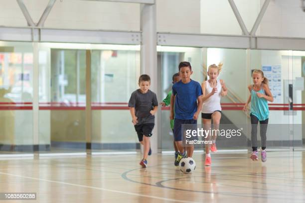 Kids playing soccer in gym