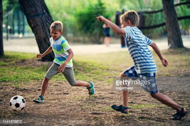 gosses jouant au soccer dans le parc. - football player photos et images de collection