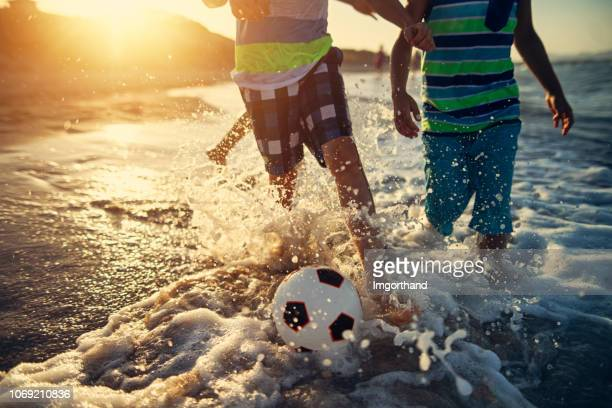 kids playing soccer on the beach - sunny stock pictures, royalty-free photos & images