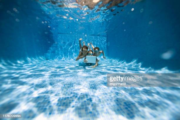 kids playing tablet underwater - kids pool games stock pictures, royalty-free photos & images