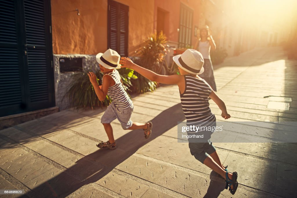 Kids playing tag in mediterranean street : Stock Photo