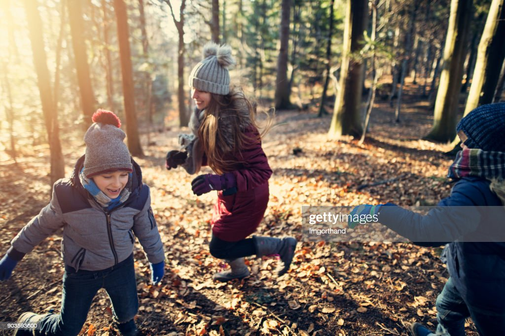 Kids playing tag in winter forest : Stock Photo