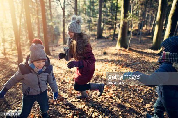 niños jugando a pillar en bosque del invierno - kids playing tag fotografías e imágenes de stock
