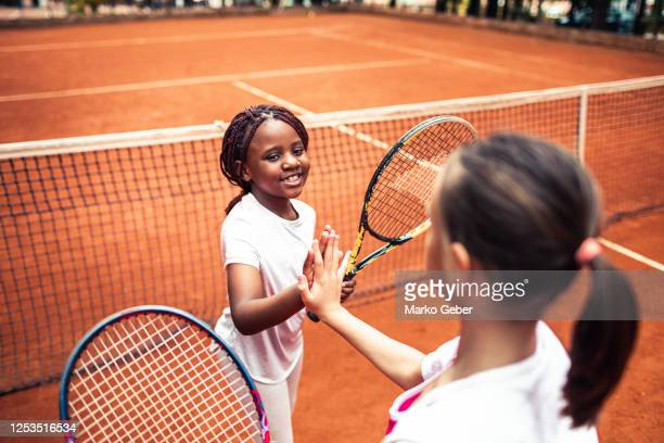 kids playing tennis high fiving - doubles stock pictures, royalty-free photos & images