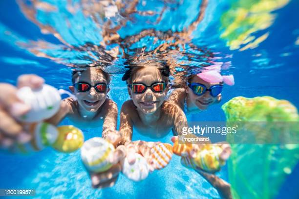 kids playing underwater during summer easter - easter egg hunt stock pictures, royalty-free photos & images