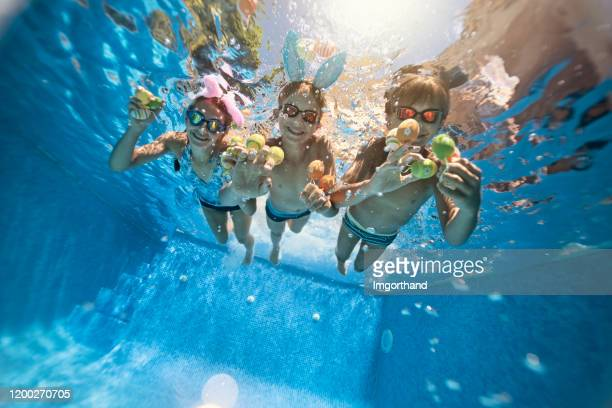 kids playing underwater during summer easter - kids pool games stock pictures, royalty-free photos & images