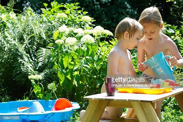 kids playing with a doll's tea set, summertime - petite fille culotte photos et images de collection
