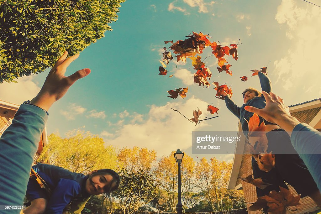 Kids playing with autumn leafs in the home yard. : Stock Photo