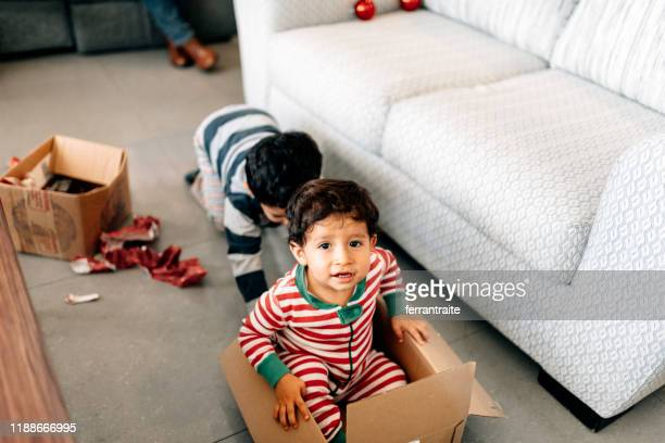 kids playing with boxes on christmas morning - 2 5 months stock pictures, royalty-free photos & images