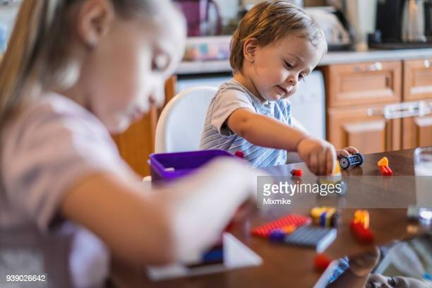 Kids playing with colorful bricks at dining table