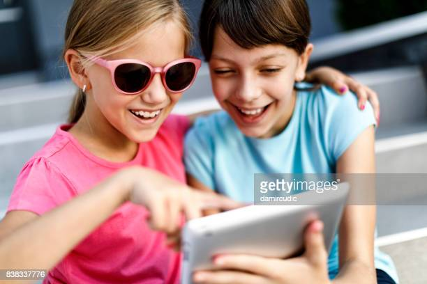 Kids playing with digital tablet outside
