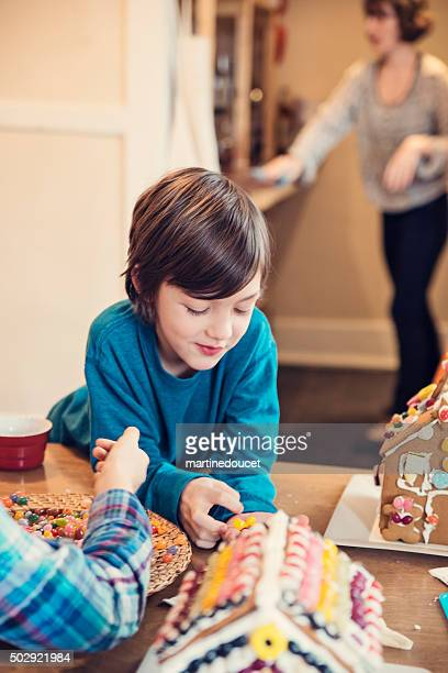 """kids playing with gingerbread house, mother cleaning in background. - """"martine doucet"""" or martinedoucet stock pictures, royalty-free photos & images"""