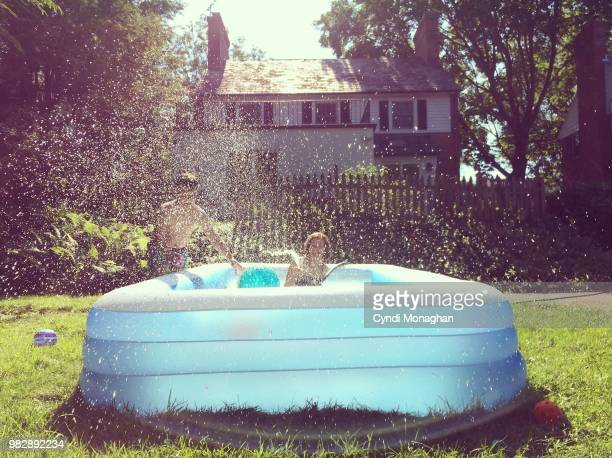 kids playing with hose and swimming pool - inflatable stock pictures, royalty-free photos & images