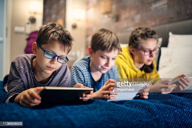 kids playing with modern mobile devices - pre adolescent child stock pictures, royalty-free photos & images