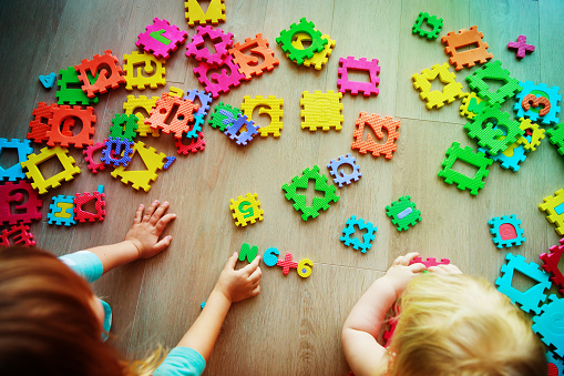 kids playing with puzzle, learning numbers and shapes 1028699780