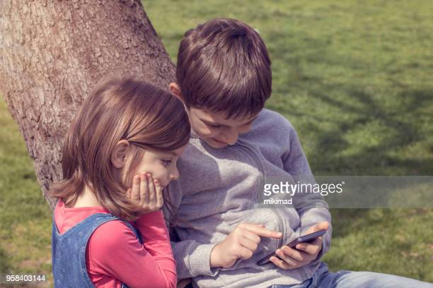kids playing with smart phone - website template stock photos and pictures