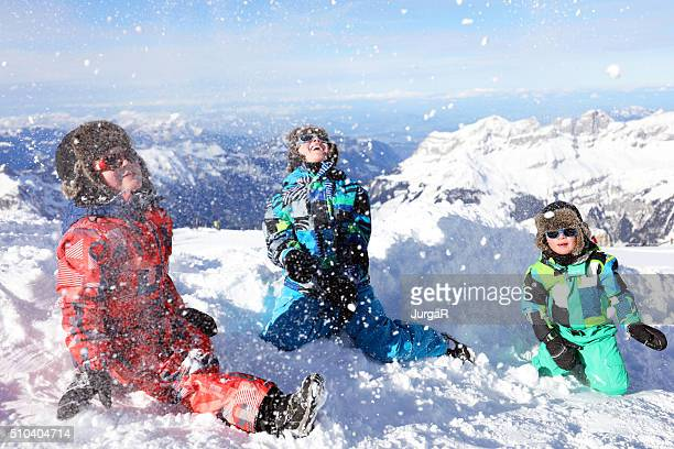 Kids Playing with Snow in Swiss Mountains in Winter