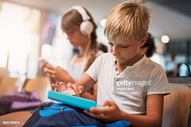 Kids playing with tablets while waiting at the airport
