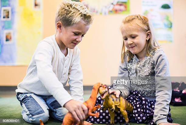 Kids playing with toy dinosaurs in kindergarten