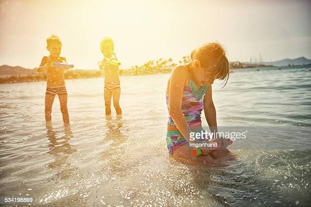 Les enfants jouer avec les pistolets à eau de mer