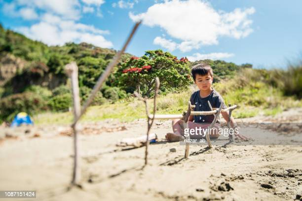 Kids playing with wood at beach.