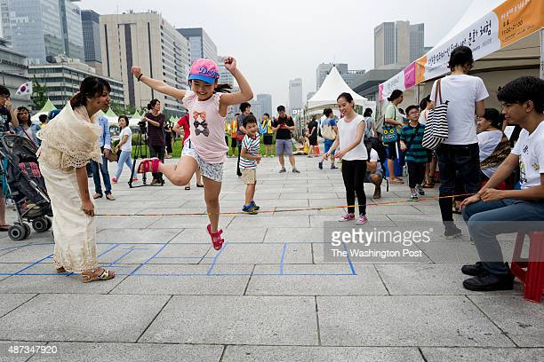 Kids plays Philippine traditional game with a elastic string at a temporal cultural experience zone on Gwanghwamun Square on Jul. 29, 2015 in Seoul,...