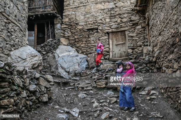 Kids pose for a photo in front of stone houses at their village at Hizan district in the southeastern province of Bitlis Turkey on February 18 2018...