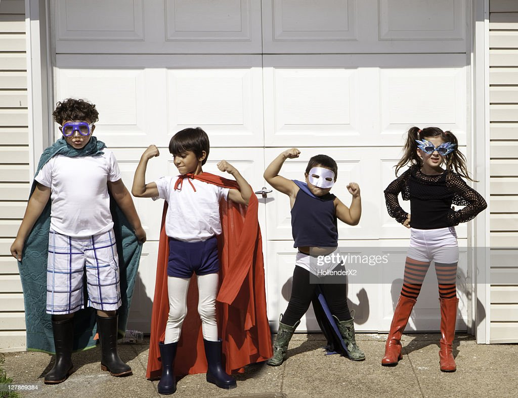 4 kids posing for camera in superhero outfits : Stock Photo