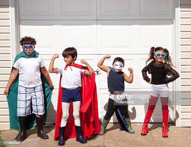 4 kids posing for camera in superhero outfits