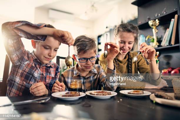 kids pouring honey over loafs of wholegrain bread - imgorthand stock photos and pictures