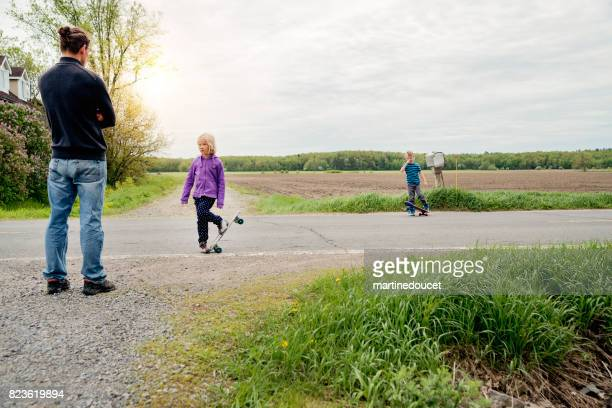 Kids practicing skateboard in rural street under dad supervision