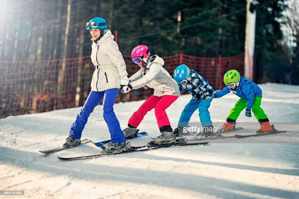 Kids practicing skiing with ski school instructor : Stock Photo
