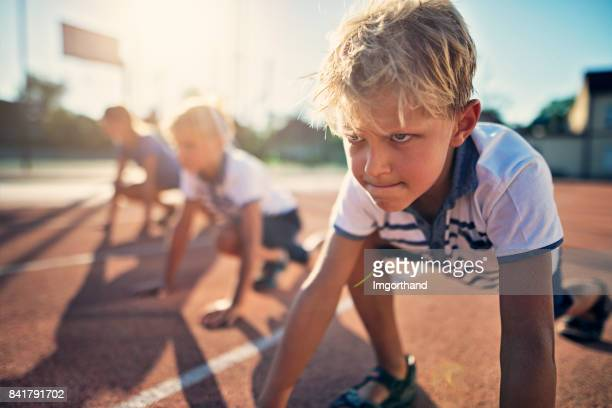 kids preparing for track run race - endurance stock photos and pictures