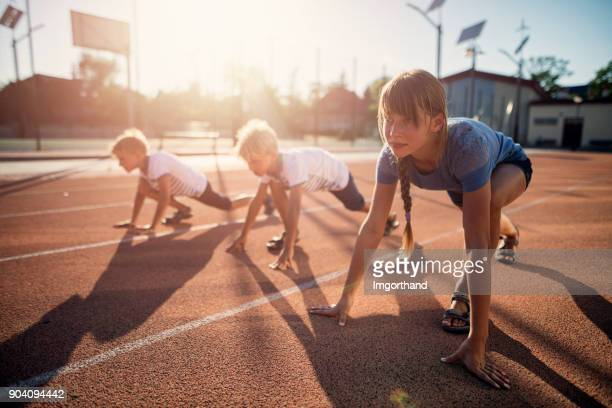 kids preparing for track run race - athletics stock photos and pictures