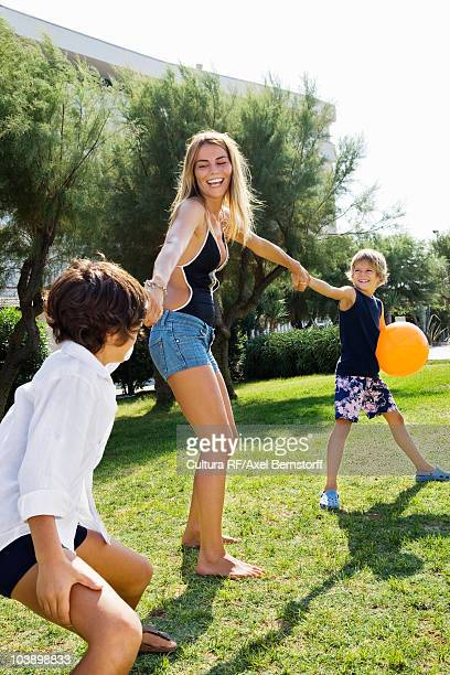 Kids pulling young woman's hand on lawn