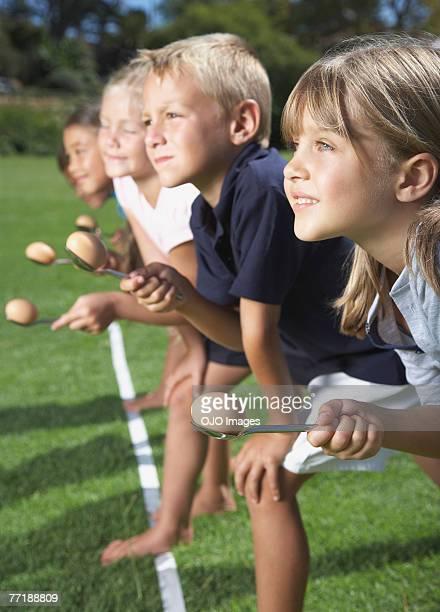 Crianças ao transporte de ovos em colheres