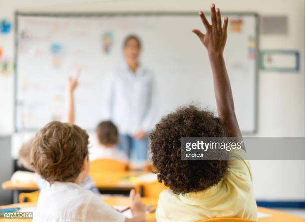 Kids raising their hands in class at the school