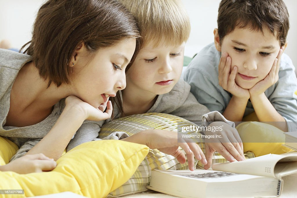 Kids reading a textbook : Stock Photo