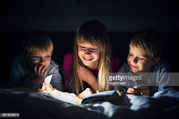 Kids reading book at night