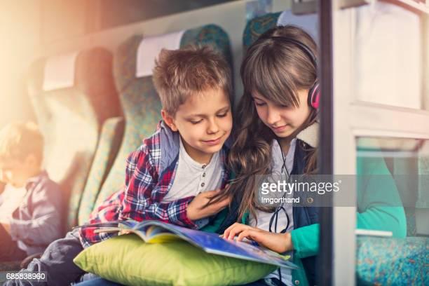 Kinder lesen Buch zusammen auf Zug