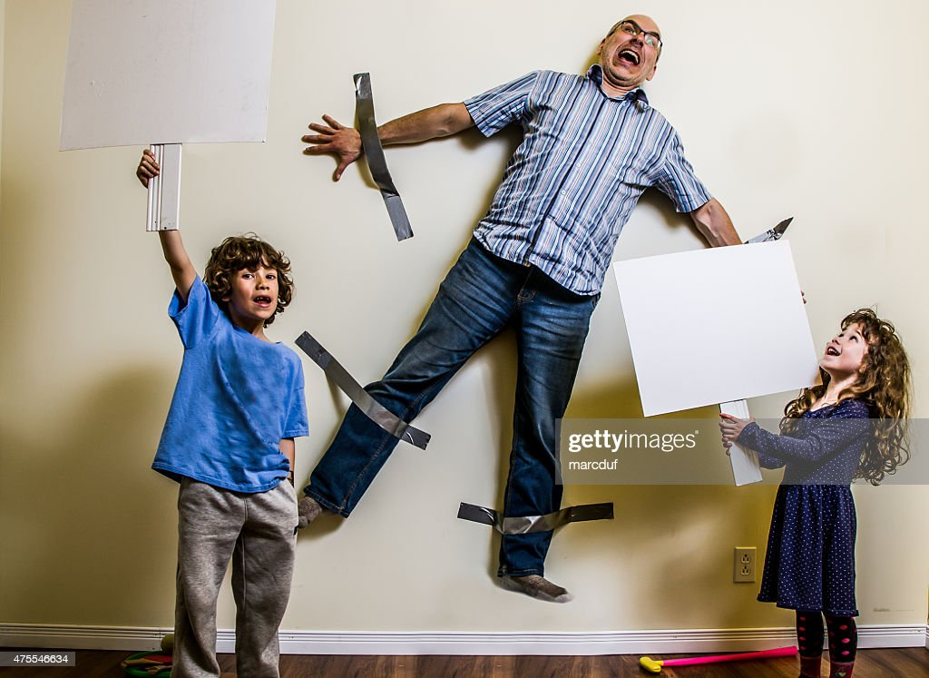 Kids rebellion led to strapping the father on wall : Stock Photo