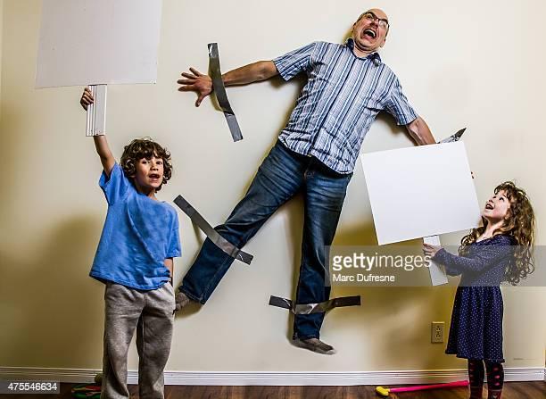 Kinder-rebellion hat zu Umgurtung geschmückt, die der Vater an der Wand