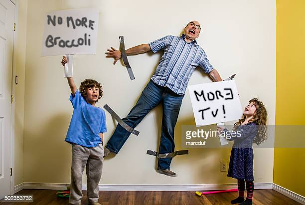 kids rebellion led to strapping the father on wall - authority stock photos and pictures