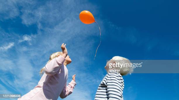 kids releasing balloon in blue sky - releasing stock pictures, royalty-free photos & images