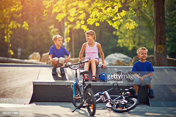 kids resting after riding bicycles on ramps - bmx cycling stock pictures, royalty-free photos & images